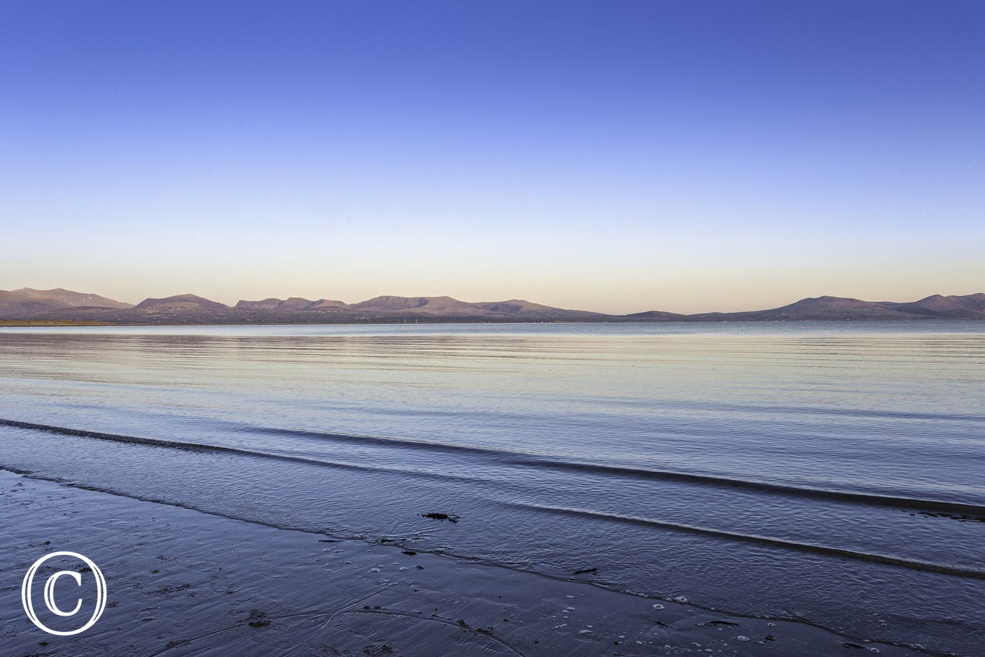 Calm sea at sunset from Newborough Beach