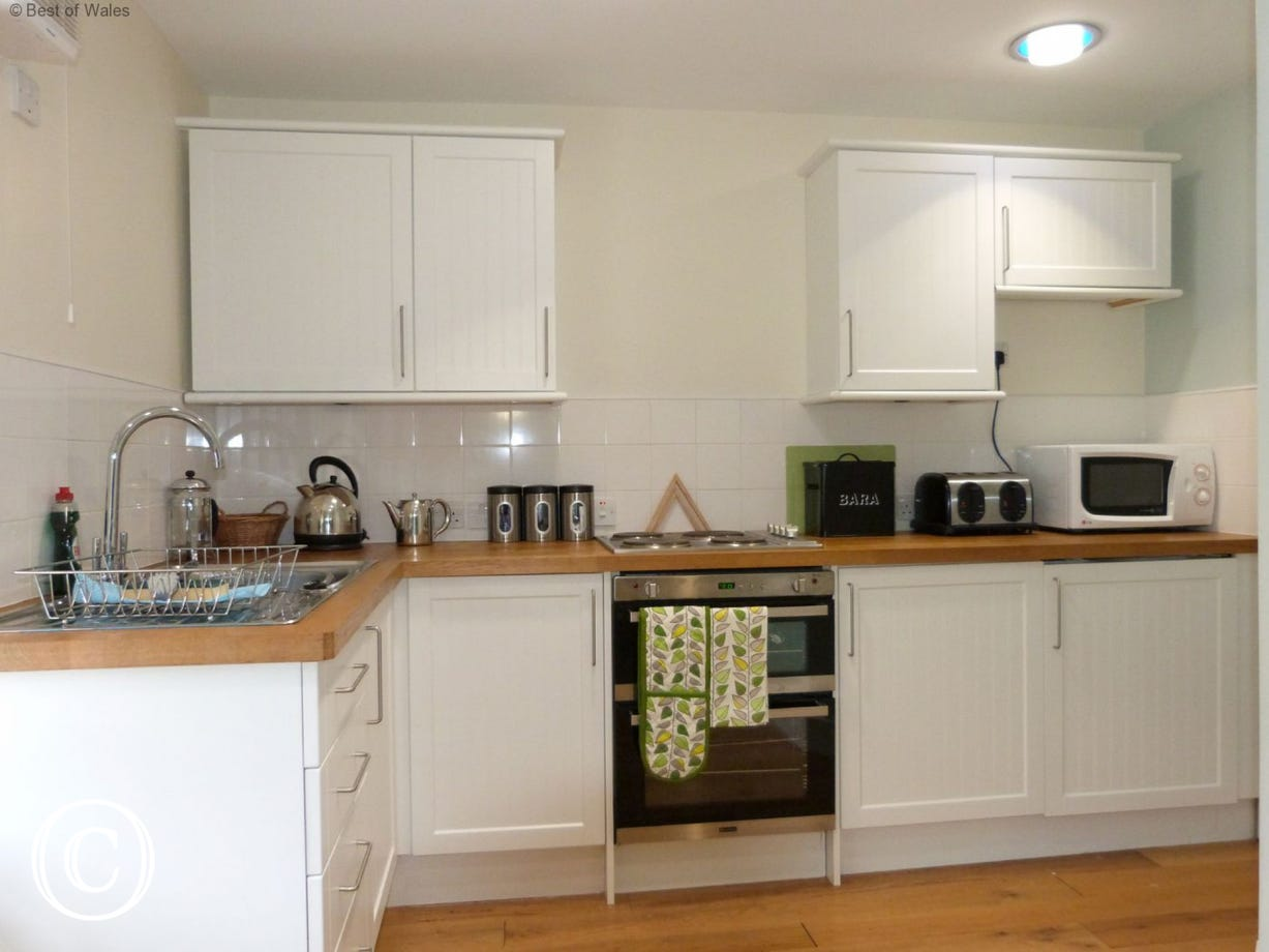 Kitchen includes electric oven and hob, microwave and fridge