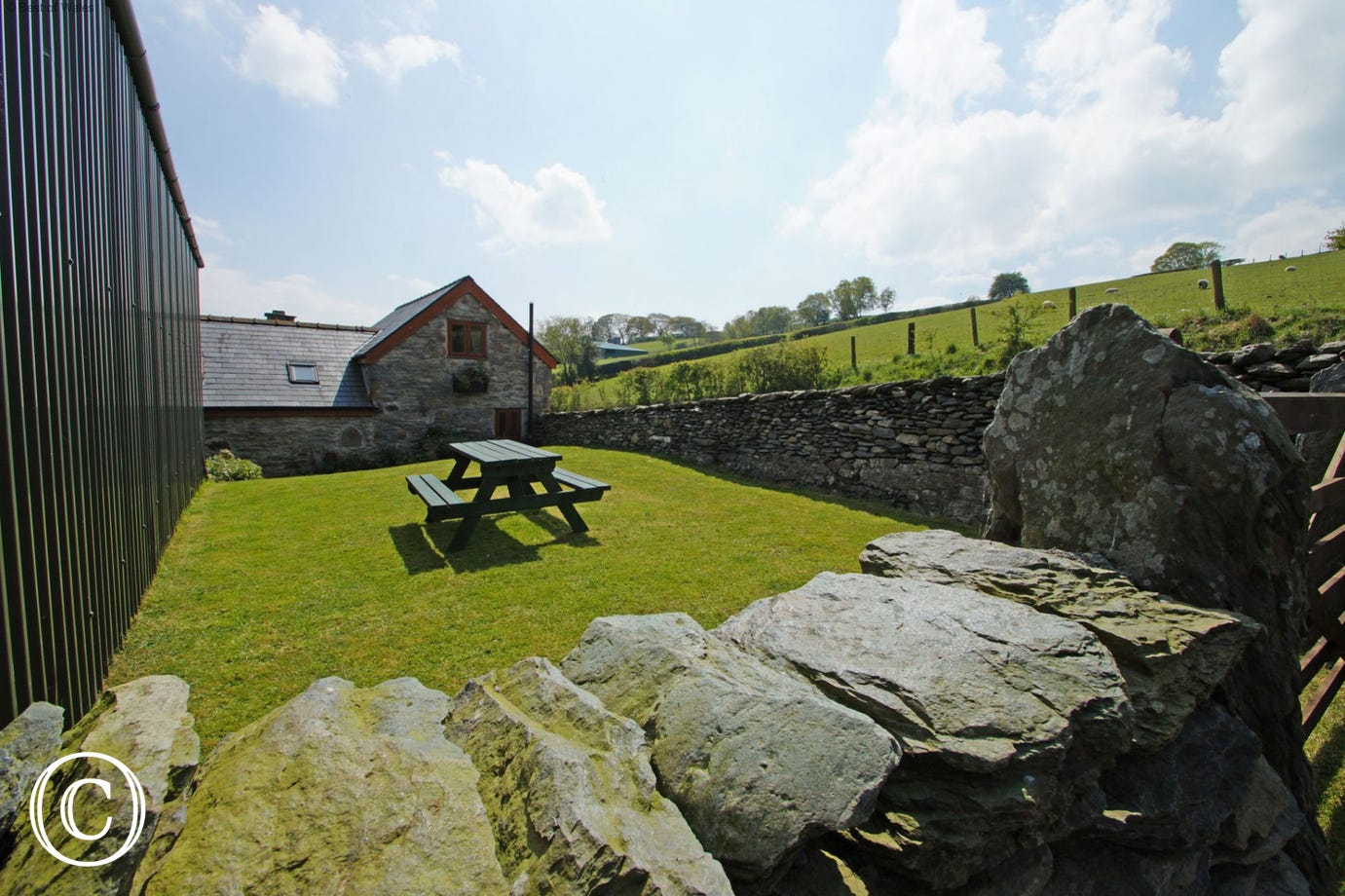 Enclosed lawn area with picnic bench at the rear of the cottage