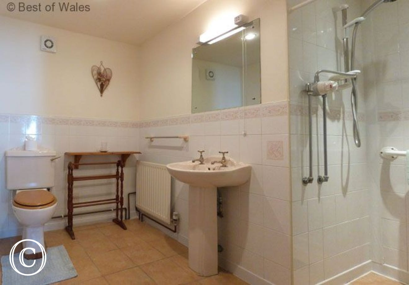 The en-suite shower room has a walk in shower with a seat.