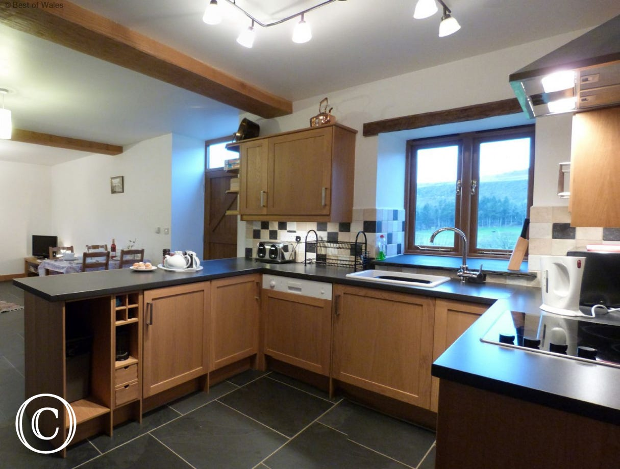 Welcoming, open plan kitchen / dining area with slate flooring.
