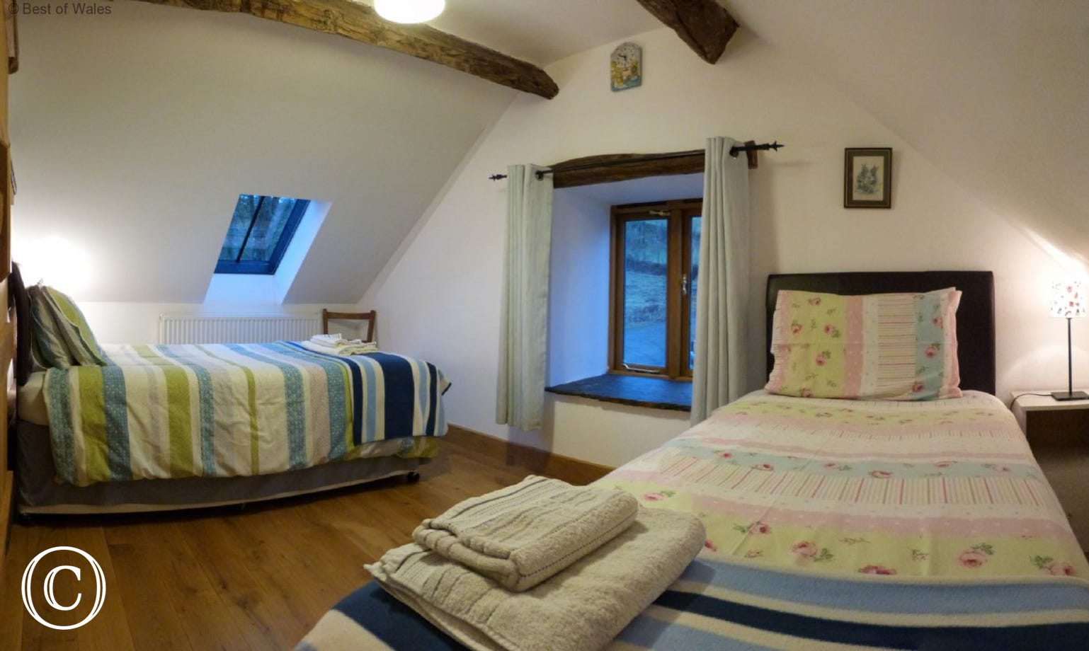 Light and airy twin bedroom with beams and oak flooring