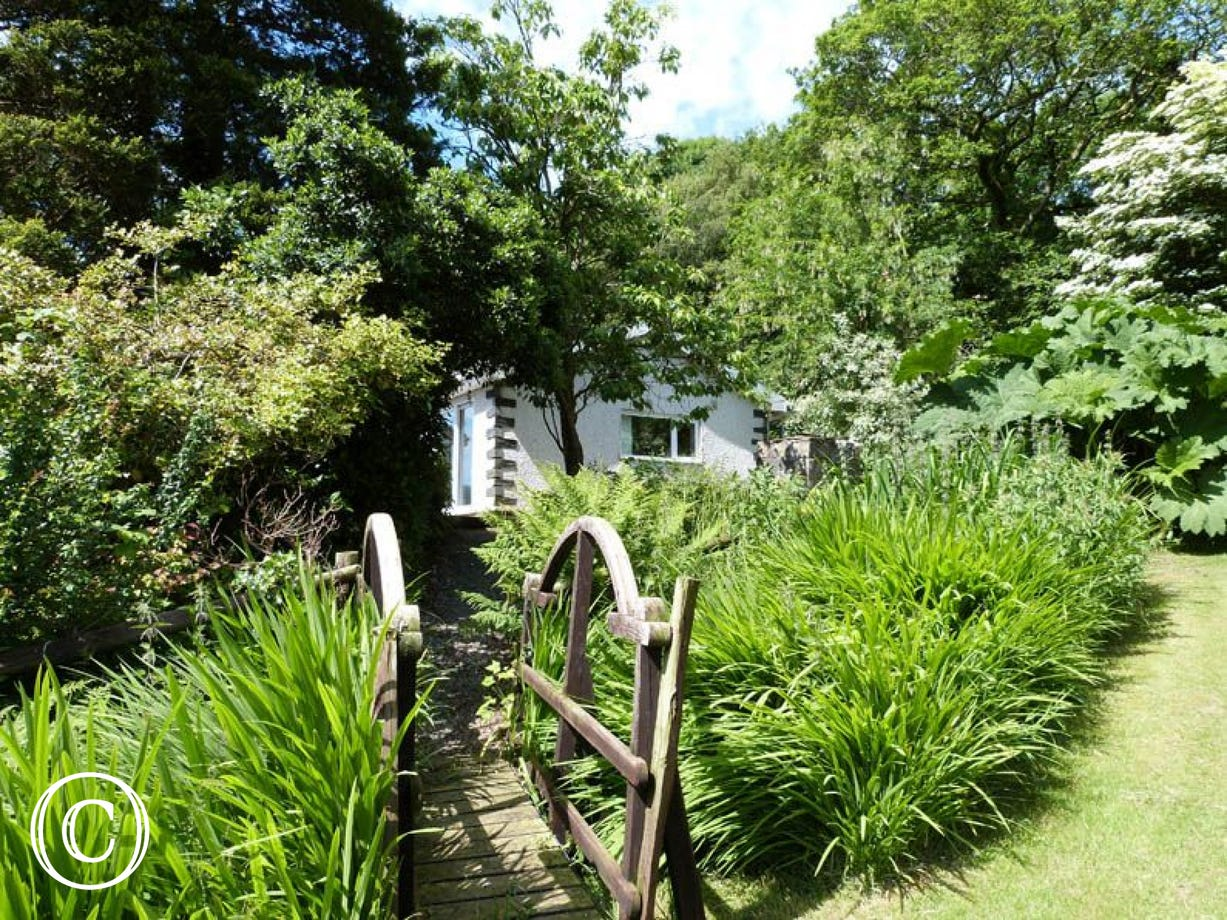 Detached cottage set within its own enclosed garden next to a little brook